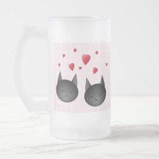 Niedliche schwarze Katzen mit Herzen, auf blassem Mattglas Bierglas