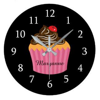 Niedlicher rosa kleiner Kuchen auf schwarzer Große Wanduhr