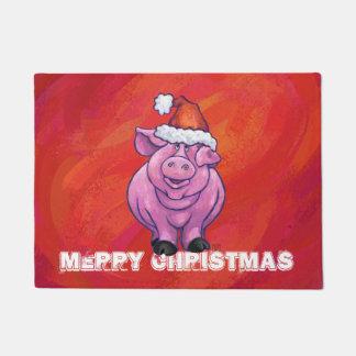 Niedliches Schwein in der Weihnachtsmannmütze auf Türmatte