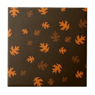 Orange Herbst-Eichen-Blätter gegen dunkles Brown Keramikfliese