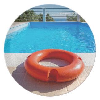 Orange Lebenboje am blauen Swimmingpool Melaminteller