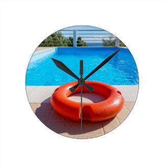 Orange Lebenboje am blauen Swimmingpool Runde Wanduhr