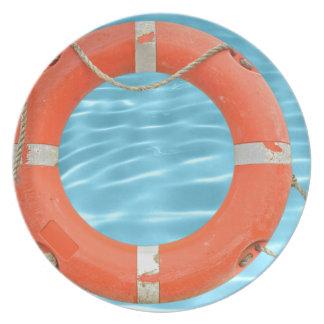 Orange lifebuoy über Swimmingpool-Wasser backgroun Melaminteller