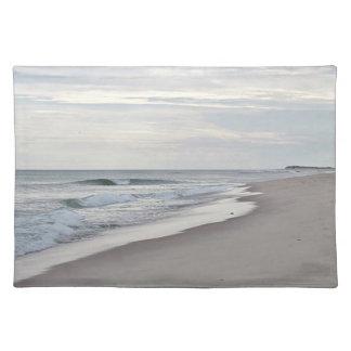 Ozeanwellen waschen sich auf einen sandigen Strand Tischset