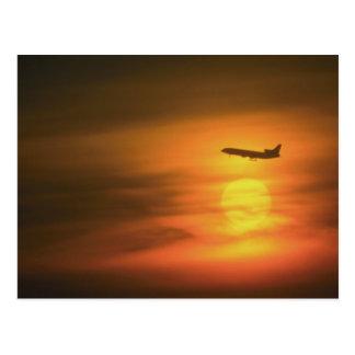 Passagierflugzeug am Sonnenuntergang, auf Weg nach Postkarte