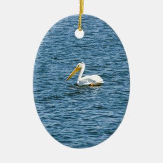 Pelikan, der im blauen Wasser schaufelt Ovales Keramik Ornament