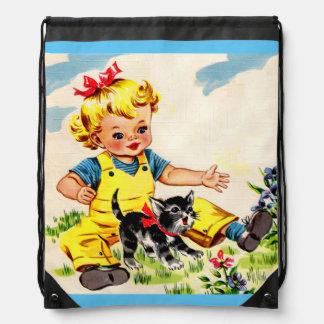 petite fille adorable avec le petit chaton sac avec cordons