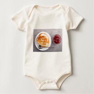 Pfannkuchen und eine Glasschale mit Baby Strampler