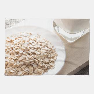 Platte mit trockenem Getreide und einem Glas Milch Handtuch