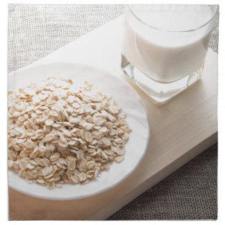 Platte mit trockenem Getreide und einem Glas Milch Serviette