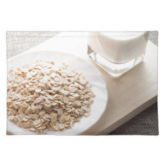 Platte mit trockenem Getreide und einem Glas Milch Stofftischset