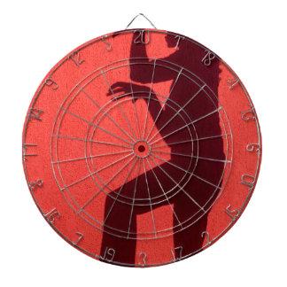 Profilschatten der Frau auf roter Wand Dartscheibe