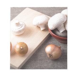 Rohe Champignonpilze und -zwiebeln auf der Tabelle Notizblock