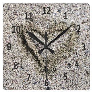 Romantisches Herz im Sand-Foto Quadratische Wanduhr