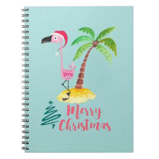 Rosa Flamingo in einer Weihnachtsmannmütze durch Spiral Notizblock