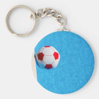 Rot-weißer Wasserball, der in Swimmingpool Schlüsselanhänger