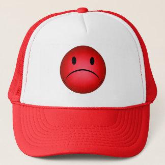 Rotes Frownie stellen Hut gegenüber Truckerkappe