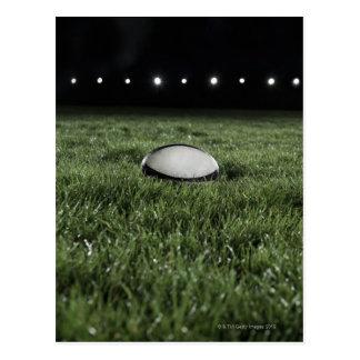 Rugbyball, der auf der Grasneigung von a sitzt Postkarte