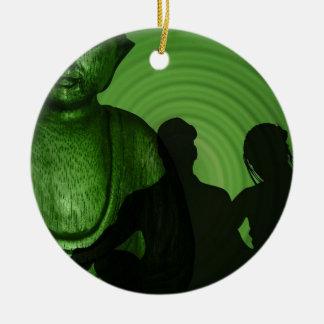 Schatten der Menschen vor Buddha im grünen Keramik Ornament