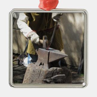 Schmied, der manuell das flüssige Metall schmiedet Quadratisches Silberfarbenes Ornament