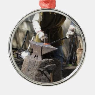 Schmied, der manuell das flüssige Metall schmiedet Rundes Silberfarbenes Ornament