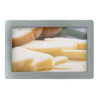 Schneiden Sie Scheiben des Käses auf einer Rechteckige Gürtelschnalle