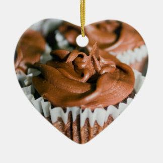 Schokoladen-mattierte kleine Kuchen auf einem Keramik Herz-Ornament