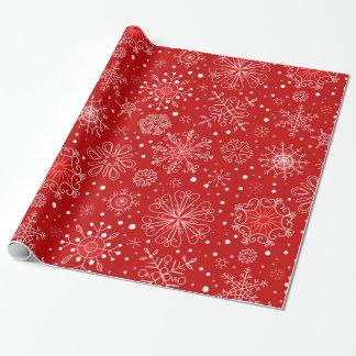 Schöne Schneeflocken auf rotem Geschenkpapier