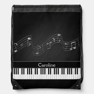 Schwarz-weiße Klavier-Schlüssel und musikalische Turnbeutel