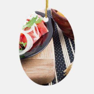 Schwarze Platte mit frischem Salat der Tomaten, Ovales Keramik Ornament