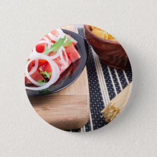 Schwarze Platte mit frischem Salat der Tomaten, Runder Button 5,1 Cm