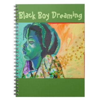 Schwarzer Junge, der Notizbuch träumt Spiral Notizblock
