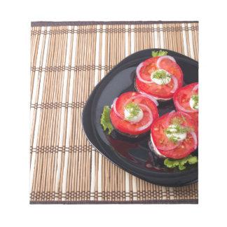 Schwarzer Teller mit geschnittenen Tomaten und Notizblock