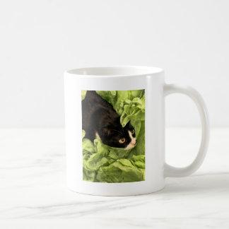 Smokings-Miezekatze, die im Seidenpapier sich Kaffeetasse