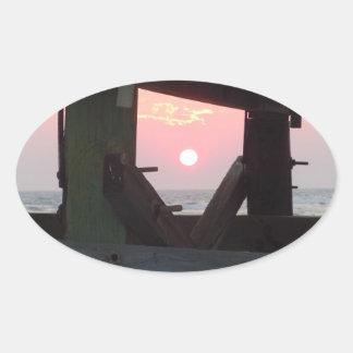 Sonnenuntergang durch den Pier - Eichen-Insel, NC Ovaler Aufkleber