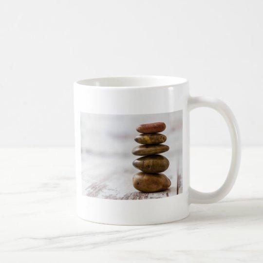 Stapel der Dunkelheit färbte Steine auf weißem Kaffeetasse