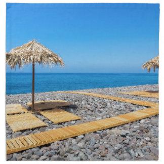 Strandschirme mit Weg und Steine an der Küste Stoffserviette