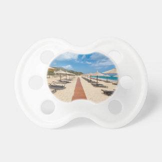 Strandschirme und Nichtstuer in griechischem Meer Schnuller