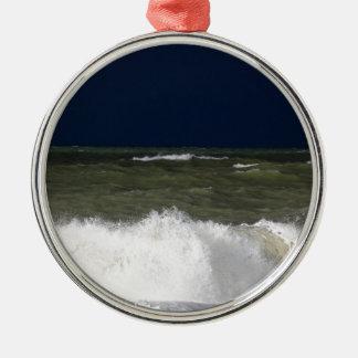 Stürmisches Meer mit Wellen und ein dunkelblauer Rundes Silberfarbenes Ornament