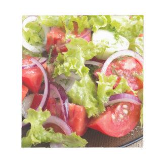 Transparente Platte mit Gemüsesalatnahaufnahme Notizblock