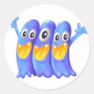Trois monstres bleus espiègles sticker rond
