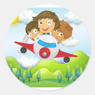 Un avion avec trois enfants espiègles sticker rond