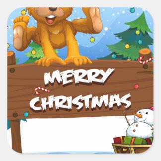 Un ours espiègle jouant près de Noël signboar Sticker Carré