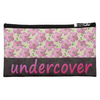 Undercover rosa mit BlumenBlumen auf irgendeiner Kosmetiktasche