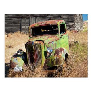 Verrostendes Auto vor verlassenem Bauernhof Postkarte