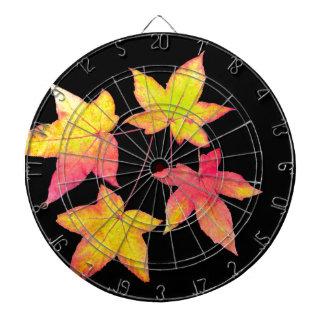 Vier farbiges Herbst-Blätter auf schwarzem Dartscheibe