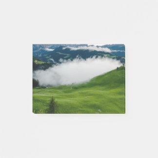 Volle grüne Gebirgsspitze mit Wolken unten Post-it Klebezettel
