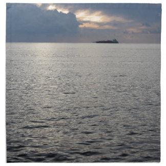Warmer Seesonnenuntergang mit Frachtschiff am Stoffserviette