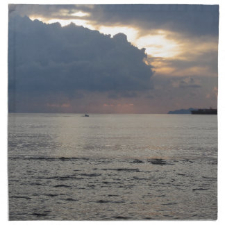 Warmer Seesonnenuntergang mit Frachtschiff und Stoffserviette