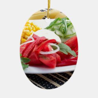 Weiße Platte mit Scheiben der frischen Tomaten Ovales Keramik Ornament